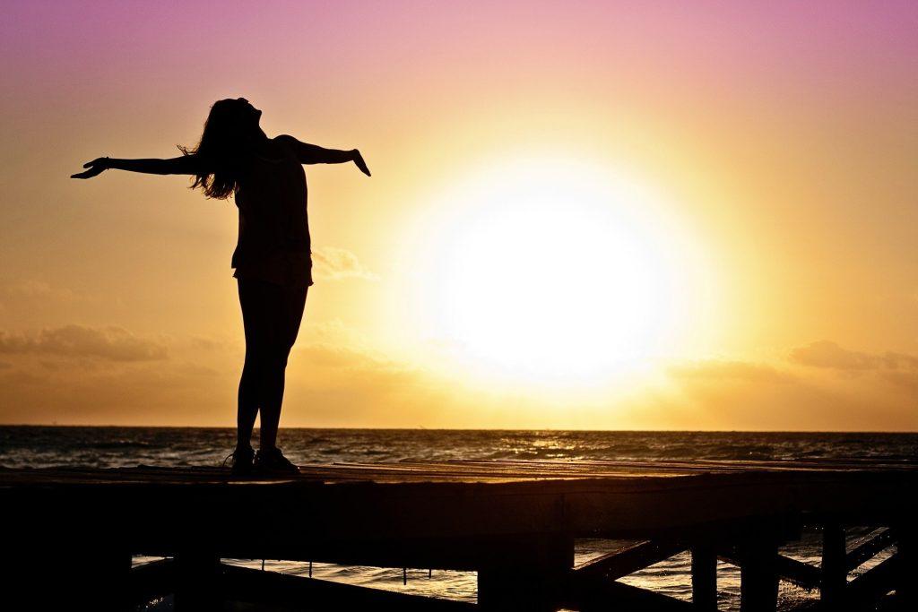 Imagem mostra uma mulher de braços abertos em uma praia.