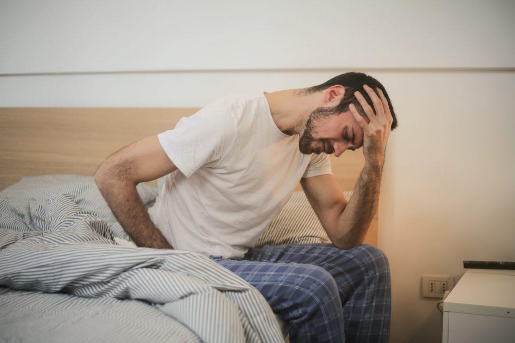 Imagem mostra um homem com aparente dor ao levantar.