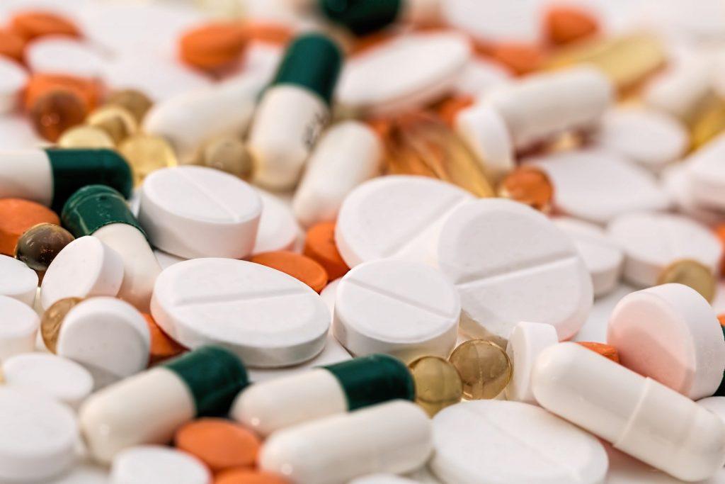 Imagem mostra diversos comprimidos, cápsulas, seringas e outros itens médicos.
