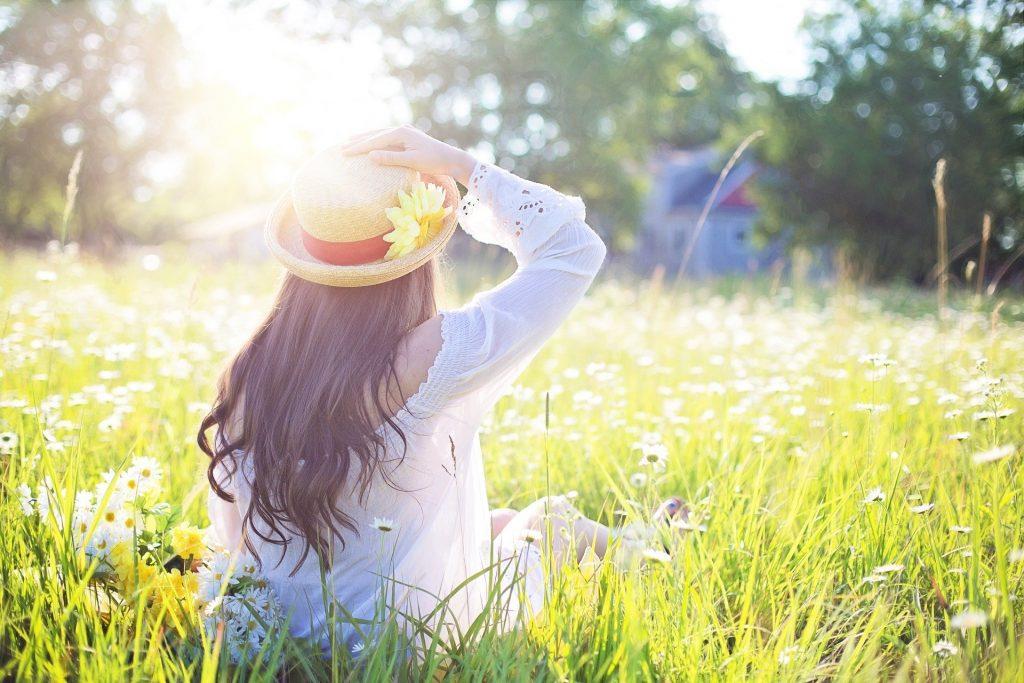 Mulher de chapéu em um campo sob o sol.