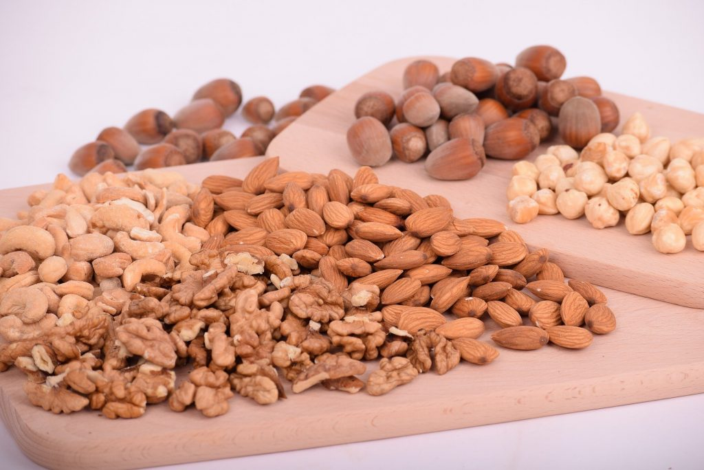 Imagem mostra vários alimentos como amendoins, amêndoas e nozes.