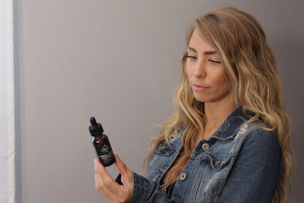 Imagem de uma mulher segurando um frasco de vitamina D.