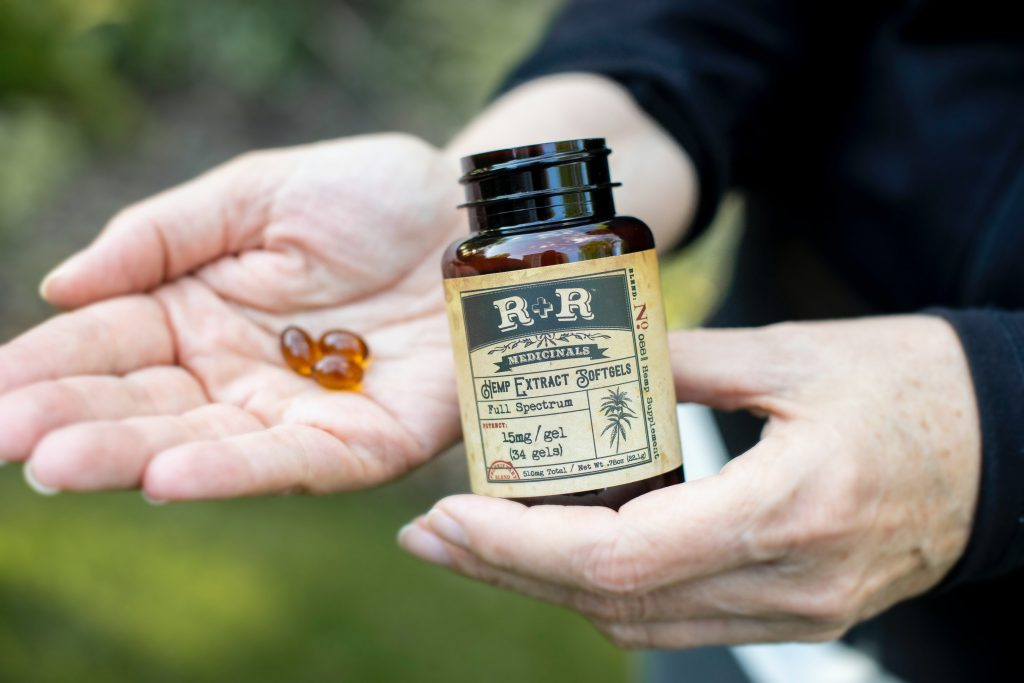 Imagem de uma pessoa segurando cápsulas de vitamina E.